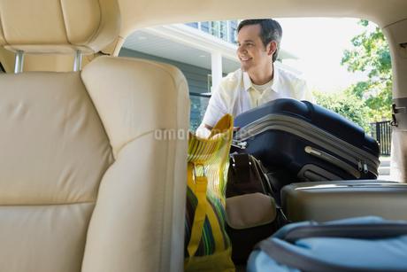 Smiling man loading luggage into back of minivanの写真素材 [FYI02292206]