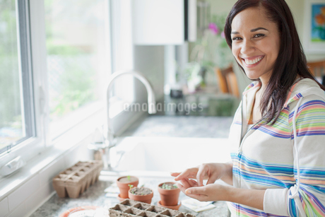 pretty latino woman planting seedsの写真素材 [FYI02292222]
