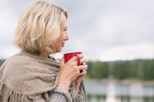 mature woman having coffee while looking out over waterの写真素材 [FYI02292226]