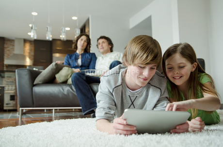 family enjoying movie night and technology togetherの写真素材 [FYI02292245]