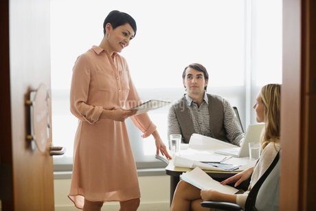 Businesswoman talking with colleagues in officeの写真素材 [FYI02292281]