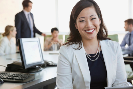 Portrait of businesswoman with colleagues in board roomの写真素材 [FYI02292321]