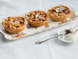 Individual apple tarts arranged on trayの写真素材 [FYI02292322]