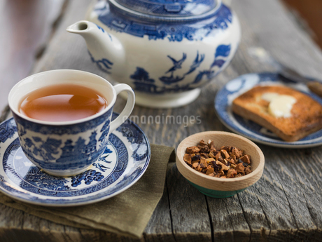 Cup of tea and kettle on wooden tableの写真素材 [FYI02292340]