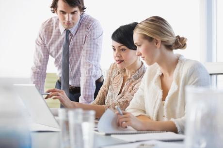 Business people sharing laptop at conference table in board roomの写真素材 [FYI02292392]