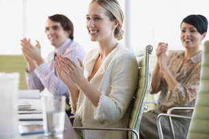 Colleagues applauding together at conference tableの写真素材 [FYI02292432]