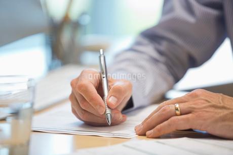 Businessman writing on document at deskの写真素材 [FYI02292452]