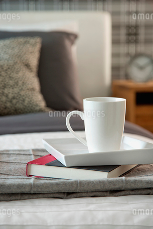 Coffee mug and book on bed at homeの写真素材 [FYI02292564]