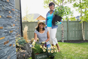 Portrait of mother and adult daughter holding potted plants in yardの写真素材 [FYI02292579]