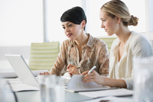 Businesswomen working on laptop togetherの写真素材 [FYI02292586]