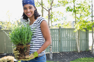 Pretty mid adult woman holding plant outdoorsの写真素材 [FYI02292737]