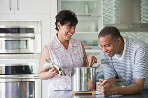 Mature man looking in cooking pot while wife stirsの写真素材 [FYI02292837]