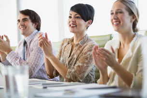 Business people applauding while sitting at conference tableの写真素材 [FYI02292862]