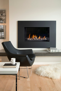 Black armchair by fireplace in contemporary living roomの写真素材 [FYI02292943]