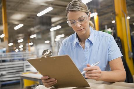 Worker analyzing checklist in warehouseの写真素材 [FYI02293019]