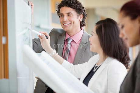 Businesswoman writing on whiteboard while standing with colleaguesの写真素材 [FYI02293027]