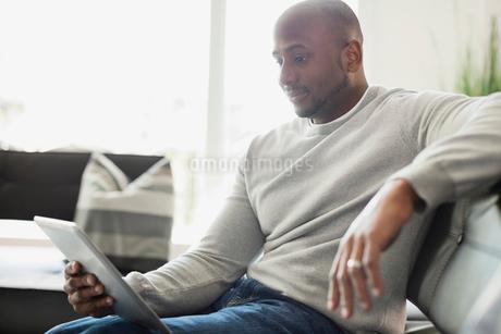 Man using digital tablet while sitting on sofaの写真素材 [FYI02293112]