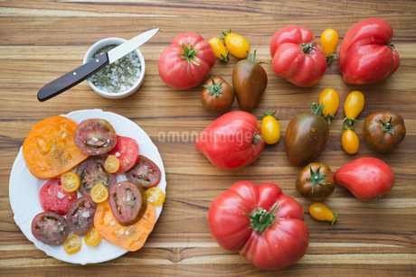 Whole and sliced Tomatoes on table with sea saltの写真素材 [FYI02293115]
