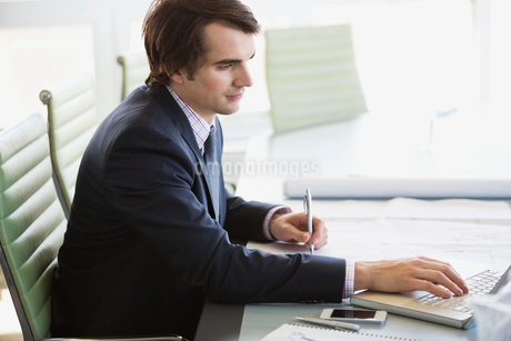 Side view of businessman using laptop at conference tableの写真素材 [FYI02293124]