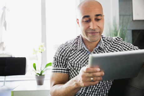 Man using digital tablet while sitting at homeの写真素材 [FYI02293128]