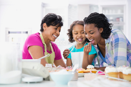 Girl feeding cupcake to her mother while grandmother looks onの写真素材 [FYI02293182]