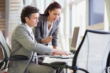 Businessman and businesswoman using desktop PC together in officeの写真素材 [FYI02293184]