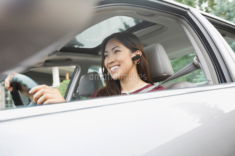 Woman with Wireless Headset driving carの写真素材 [FYI02293215]