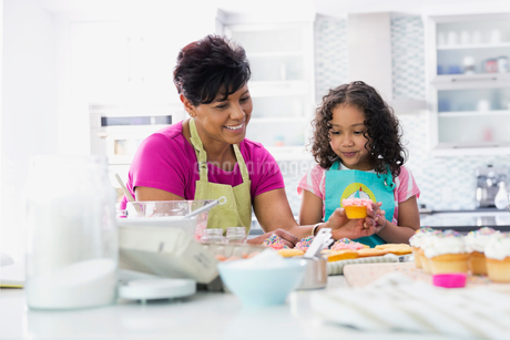 Grandmother and granddaughter decorating cupcakes in kitchenの写真素材 [FYI02293283]