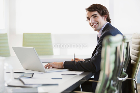 Portrait of young businessman sitting with laptop at conference tableの写真素材 [FYI02293436]