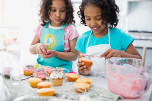 Sisters icing cupcakes together in kitchenの写真素材 [FYI02293446]