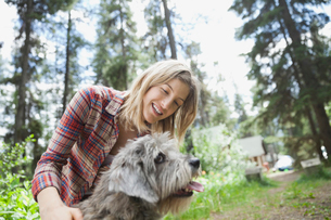Woman petting dog outdoorsの写真素材 [FYI02293460]