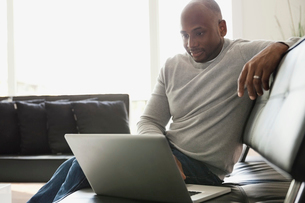 Man using laptop while sitting on sofa at homeの写真素材 [FYI02293613]