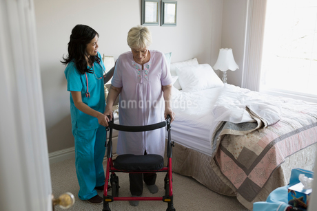 Home caregiver helping senior woman with walker in bedroomの写真素材 [FYI02293619]