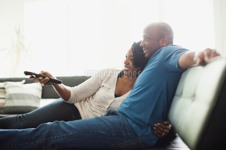 Couple relaxing while watching TV at homeの写真素材 [FYI02293624]