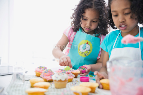 Little sisters decorating cupcakes in kitchenの写真素材 [FYI02293664]