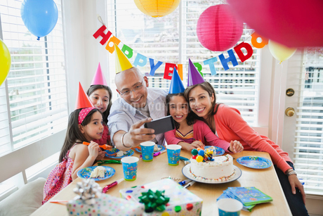 Family of five taking self portrait at birthday celebrationの写真素材 [FYI02293684]
