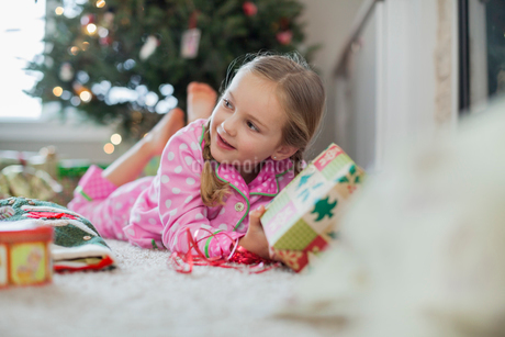 Girl opening Christmas gift at homeの写真素材 [FYI02293702]