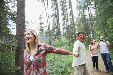 Woman leading blindfolded man through the forestの写真素材 [FYI02293707]