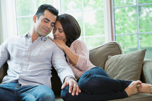 Romantic mid adult couple relaxing on sofa at homeの写真素材 [FYI02293751]