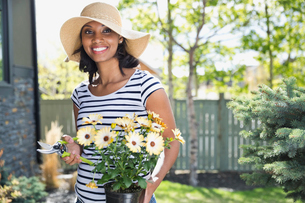 Portrait of woman with potted flowers and pruning shearsの写真素材 [FYI02294013]