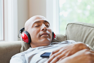 Man listening to music while relaxing on sofaの写真素材 [FYI02294052]