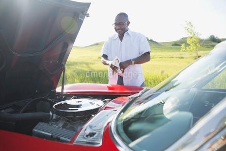 Smiling senior man standing by open hood of convertibleの写真素材 [FYI02294112]
