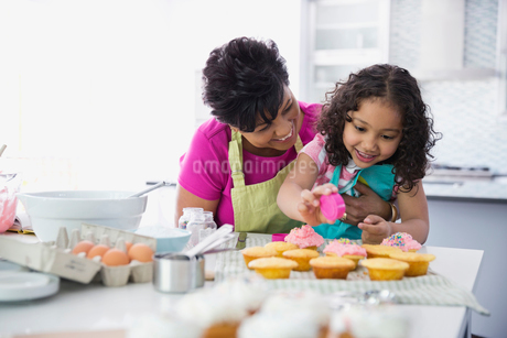 Little girl putting sprinkles on cupcakes with grandmother's helpの写真素材 [FYI02294142]