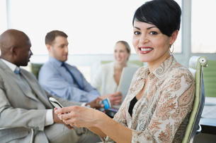 Businesswoman holding mobile phone in meeting roomの写真素材 [FYI02294158]