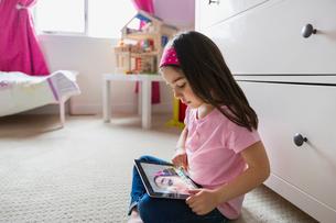 Little girl using digital tablet while sitting on floorの写真素材 [FYI02294176]