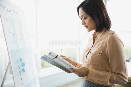 Businesswoman reading file in boardroomの写真素材 [FYI02294201]