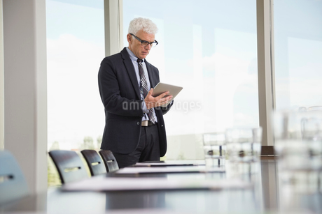 Businessman using digital tablet in board roomの写真素材 [FYI02294215]