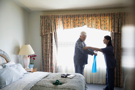 Home caregiver helping senior man exercise with resistance bandの写真素材 [FYI02294245]