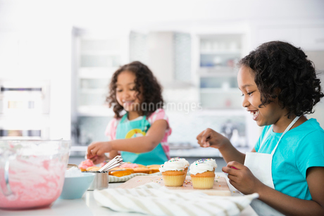 Little girl adding sprinkles to cupcakes with sisterの写真素材 [FYI02294254]