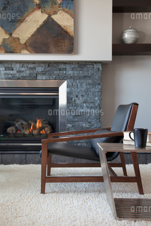 Armchair by fireplace in contemporary living roomの写真素材 [FYI02294256]